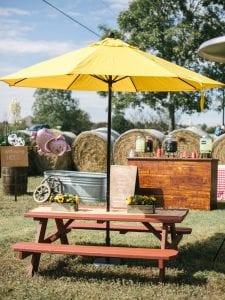 Yellow umbrella covers a brown picnic table, with two sunflower arrangements on it, and haybales in the background
