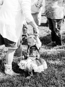 Young girl in cowboy outfit being held by her mother