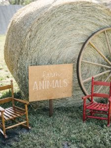 """Two rocking chairs with a """"Farm Animal"""" sign positioned in between, and large haybale in the back"""