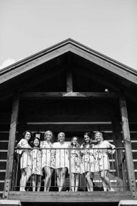 Bride and her bridemaids smiling at the camera in their bathrobes while standing at a patio