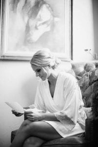 Bride in her bathrobe, sitting on a chair reading a letter the groom wrote her