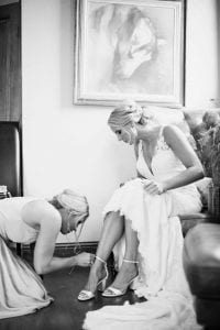 Bridesmaid helping the bride with her sandal straps