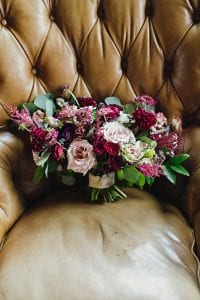 Red, fuschia and blush bridal bouquet, resting on a chair
