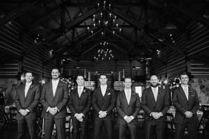 Groom and groomsmen standing in a row smiling at the camera