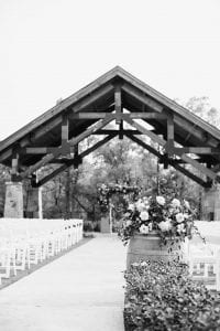 Ceremony shot with an altar at the front, white garden chairs and a floral arrangement on a wine barrel at the start of the aisle