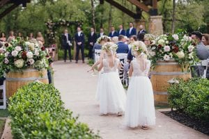 Three flower girls throwing petals and walking down the aisle at a wedding