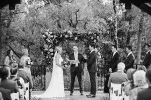 Bride and groom laughing and smiling as they stand at the altar with their bridal party and officiant, as guests look on