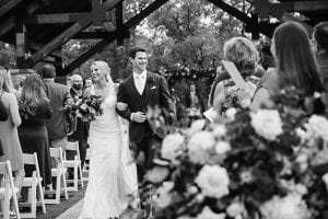 Bride and groom laughing and smiling as they exit from their wedding ceremony, as guests stand and clap