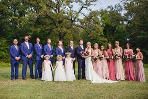 bride and groom smiling with their bridesmaids, groomsmen and flower girls