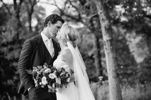 Bride and groom kiss while the bride holds her bridal bouquet in a forrest