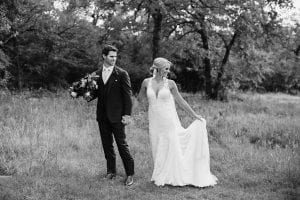 Groom holding the bride's bouquet as she's holding her dress in a field