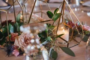 Geometric votives surrounded by flowers as part of a wedding table arrangement