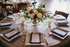 Blush, burgundy and white floral arrangement on a guest round table, with blue napkins, a menu card and brown garden chairs