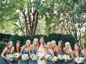Bride and her bridesmaids wearing dusty blue carrying their wedding bouquets