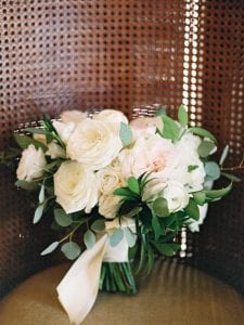 White and blush bridal bouquet resting on a chair