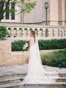 Bride standing on stairs, holding her bridal bouquet and wearing her wedding gown and veil