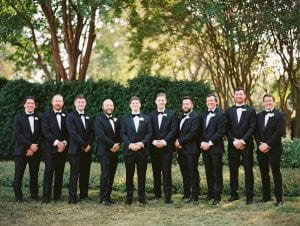 Groom and his nine groomsmen smiling and posing for the camera
