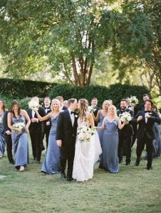 bride and groom kissing while their bridal party walks behind them cheering and laughing
