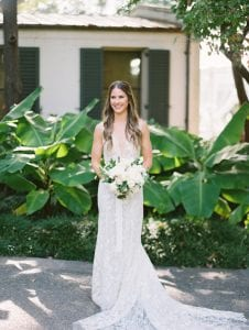 Bride smiling on her wedding day while holding her floral bouquet at the Dallas Arboretum