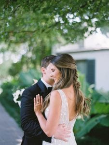 Groom gives bride a kiss on her cheek while she smiles and rests her hand on his chest