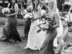Bride and her bridesmaids, on their way to the ceremony, laughing and carrying their bouquets