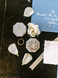 Rings of the bride and groom, arranged by flower petals and the wedding stationery suite