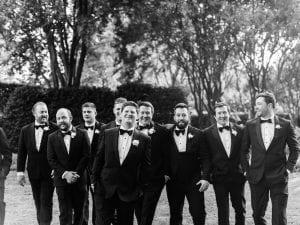 Groom and his groomsmen smiling in a garden