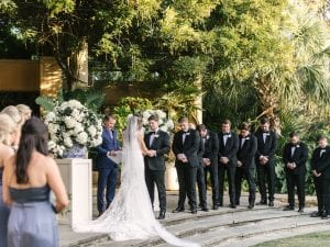 Bride, groom and their bridal party at the front of the altar at the ceremony, in prayer