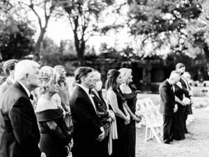 Wedding guests standing as bride and groom are at the altar