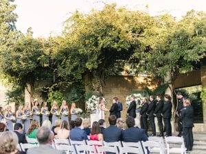 Wedding ceremony taking place at a botanical garden, with bride, groom, their bridal party and guests