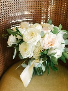 White and blush bridal bouquet resting in a chair