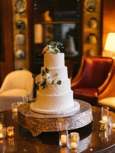 A four tier wedding cake decorated with flowers and greenery on a cake stand, surrounded by clusters of candles