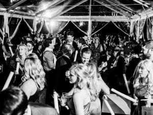 Guests dancing and mingling at a wedding reception while waving foam glowsticks