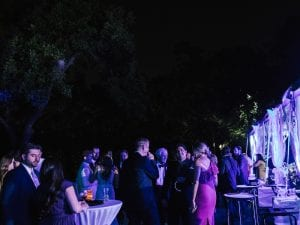 Guests dancing and mingling by a clear tent in a garden