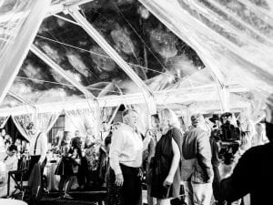 Guests dancing and mingling on the dance floor under a clear tent