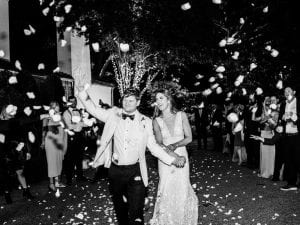 Bride and groom exiting their wedding with smiles on their faces as guests line up to toss rose petals at them
